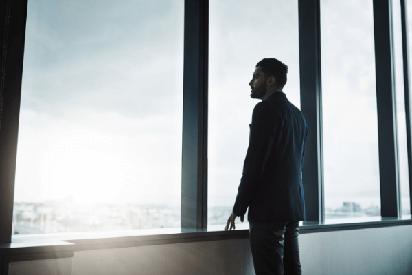 Successful leader looking out window in a volatile, uncertain, and complex work environment