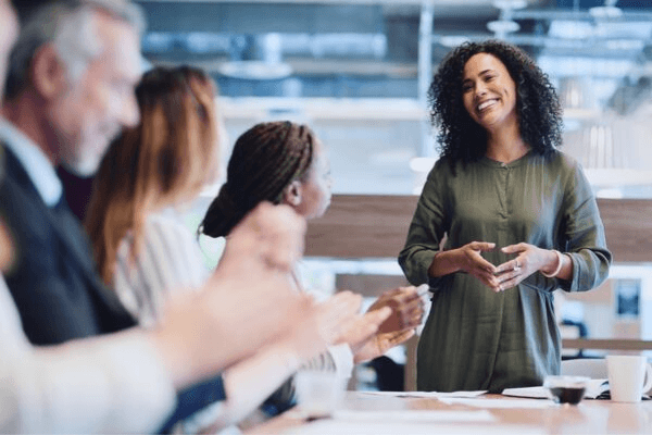 Coaching leader speaking in front of employees in office conference room