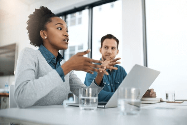 Strong female leader coaching employees in the workplace with computer