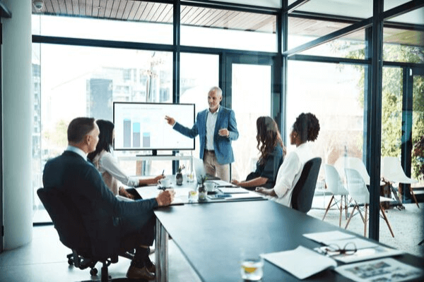 Senior leader coaching employees in conference room with screen