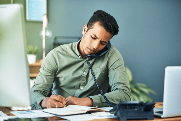 Hardworking employee working and talking on the phone in office
