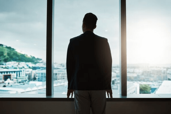 CEO looking out window in office building